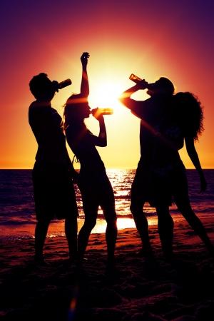 shining through: Le persone (due coppie) sulla spiaggia con una festa, bere e avere un sacco di divertimento al tramonto (solo silhouette di persone da vedere, persone con bottiglie in mano con il sole che splende attraverso)