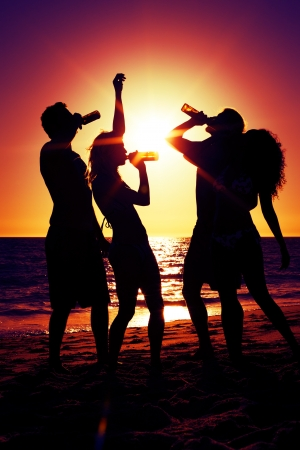 girl drinking water: People (two couples) on the beach having a party, drinking and having a lot of fun in the sunset (only silhouette of people to be seen, people having bottles in their hands with the sun shining through)