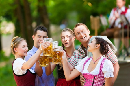 dirndl: In Beer garden in Bavaria, Germany - friends in Tracht, Dirndl and Lederhosen and Dirndl standing in front of band