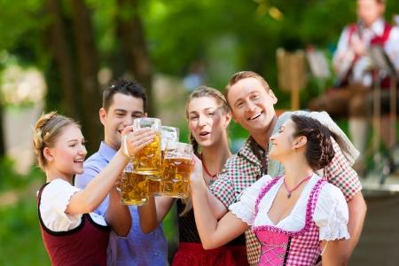 In Biergarten in Bayern, Deutschland - Freunde in Tracht, Dirndl und Lederhosen und Dirndl stehen vor der Bande