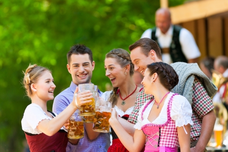 tracht: In Beer garden in Bavaria, Germany - friends in Tracht, Dirndl and Lederhosen and Dirndl standing in front of band