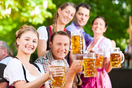 In Beer garden - friends in Lederhosen drinking a fresh beer in Bavaria, Germany photo