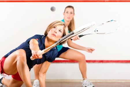 might: Two women playing squash as racket sport in gym, it might be a competition