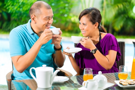 Asian couple having coffee on the porch in front of their home, in the background a tropical garden photo