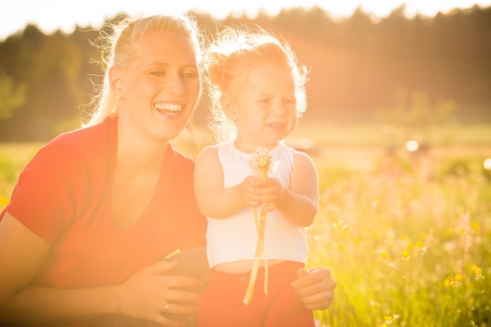 Mother with kid in the meadow and blowing dandelion seed in sunshine photo