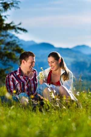 Happy Couple hiking taking a break sitting in alp meadow with mountain panorama photo