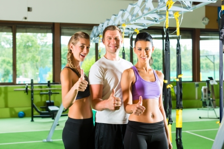 Group of people exercising with suspension trainer in fitness club or gym Stock Photo - 20904579