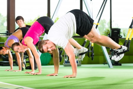 athletics training: Group of people exercising with suspension trainer in fitness club or gym