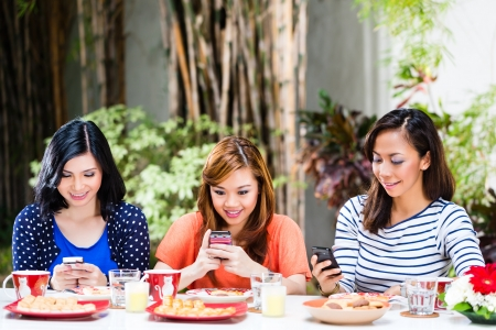 telephone together: Three Indonesian girlfriends using their mobile phones, they chat or text and read emails in a tropical environment