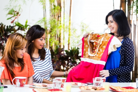 clothes interesting: Three Indonesian girlfriends, one has bought a new dress and ask the others for their opinion Stock Photo
