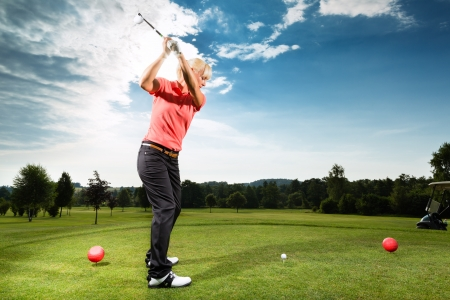 Young female golf player on course doing golf swing, she presumably does exercise Stok Fotoğraf