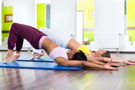 Young women doing yoga and meditation in gym for better fitness, caucasian and latina people Stock Photo - 20904601