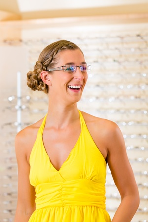 might: Young woman at optician with glasses, she might be customer or salesperson Stock Photo