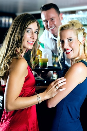 young womens: Young womens in bar or club, the bartender serve cocktails
