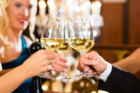 gala: Good friends - man and women, drinking wine and clinking glasses in a fine dining restaurant, each with a glass in hand, a large chandelier is in Background