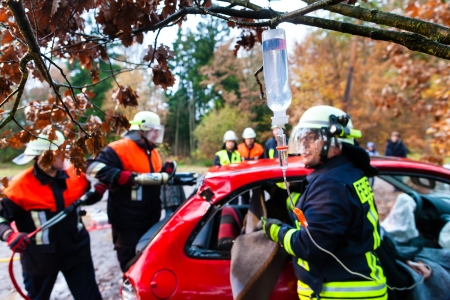 speeder: Accident - Fire brigade rescues accident Victim of a car using a hydraulic rescue tool and giving a first aid infusion