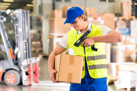 Warehouseman with protective vest and scanner, scans bar-code of package, he standing at warehouse of freight forwarding company Фото со стока