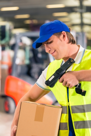 forwarding: Warehouseman with protective vest and scanner, scans bar-code of package, he standing at warehouse of freight forwarding company Stock Photo
