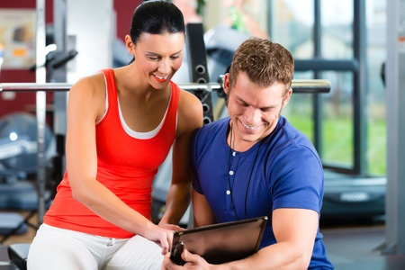 personal trainer: Woman with her personal fitness trainer in the gym