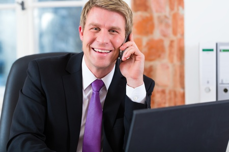 man working computer: Young lawyer working in his Office, he sitting on the desk and on the telephone is a customer or client Stock Photo