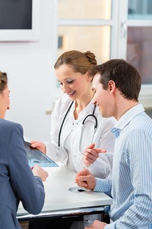 pacjent: Kobieta lekarza z jej pacjentów w klinice wyjaśniając coś Zdjęcie Seryjne