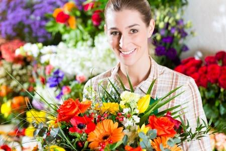 flower nursery: Female florist in flower shop or nursery presenting a bouquet of flowers Stock Photo