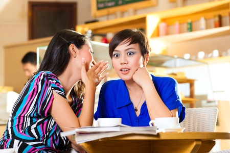 leisure time: Asian female friends enjoying her leisure time in a cafe, drinking coffee or cappuccino and talking about some things Stock Photo