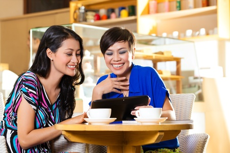 emails: Asian female friends enjoying her leisure time in a cafe, drinking coffee or cappuccino and looking at photos or emails on a tablet computer