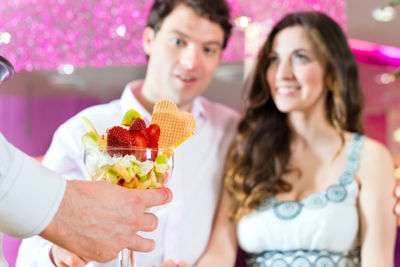 parlor: Young Couple in a Cafe or Ice cream parlor, get an ice cream served