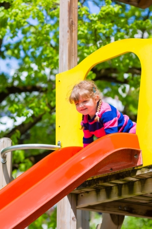 climbing frame: Little girl on a climbing frame in summer slide down