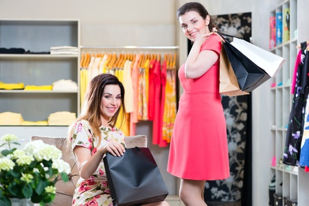 COSTUMERS: Two female friends having fun while fashion shopping in boutique or store