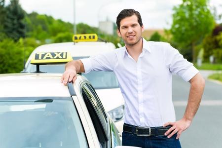 Ervaren taxichauffeur in de voorkant van zijn taxi te wachten voor een passagier