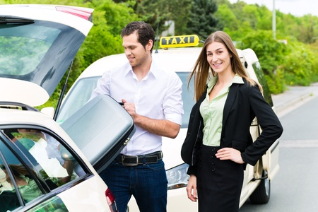 reached: Young woman standing in front of taxi, she has reached her destination, the taxi driver will help with the luggage