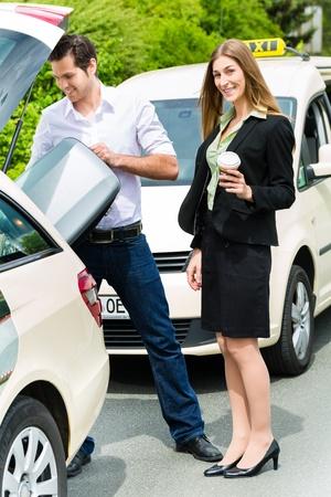 Jonge vrouw die zich in de voorkant van de taxi, heeft ze haar bestemming bereikt, zal de taxichauffeur te helpen met de bagage