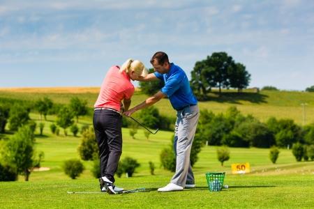 curso de capacitacion: Joven jugador de golf femenino en el Driving Range con un profesional de golf, que presumiblemente hace ejercicio Foto de archivo