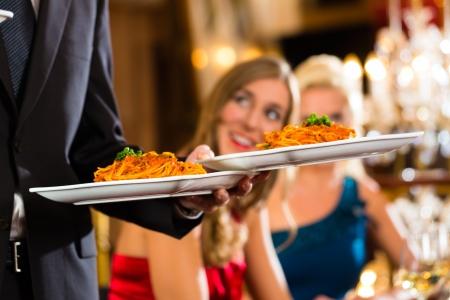 camarero: Los buenos amigos para el almuerzo en un buen restaurante, camarero sirve la cena Foto de archivo