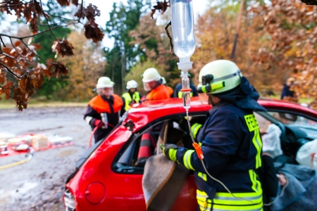 brigade: Accident - Fire brigade rescues accident Victim of a car using a hydraulic rescue tool and giving a first aid infusion