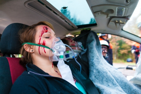 accident patient: Accident - victim in a crashed vehicle, she receives medical first aid from firefighters