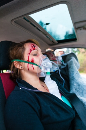Accident - victim in a crashed vehicle, she receives medical first aid from firefighters Stock Photo - 21401534