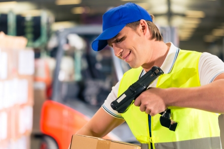 shipper: Warehouseman with protective vest and scanner, scans bar-code of package, he standing at warehouse of freight forwarding company Stock Photo