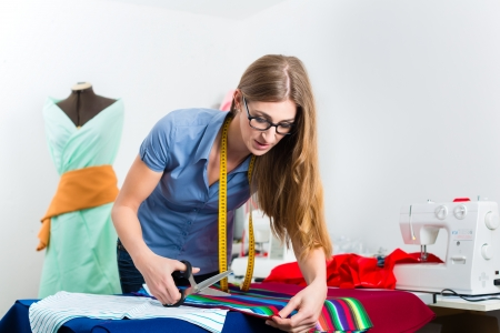 freelancer: Freelancer - Fashion designer or Tailor working on a design or draft and cutting fabrics with scissors
