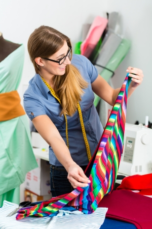 Freelancer - Fashion designer or Tailor working on a design or draft and cutting fabrics with scissors Stock Photo - 21402044