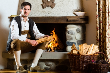 Young man in a traditional mountain hut with fireplace photo