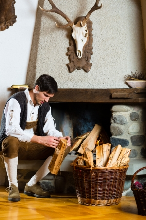 Young man in a traditional mountain hut with fireplace Stock Photo - 21402047