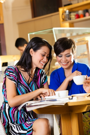 shops: Asian female friends enjoying her leisure time in a cafe, drinking coffee or cappuccino and talking about some things Stock Photo