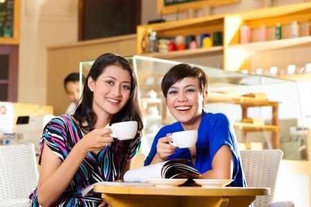Asian female friends enjoying her leisure time in a cafe, drinking coffee or cappuccino and talking about some things photo