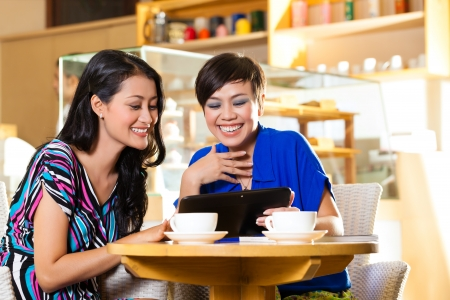 coffeeshop: Asian female friends enjoying her leisure time in a cafe, drinking coffee or cappuccino and looking at photos or emails on a tablet computer