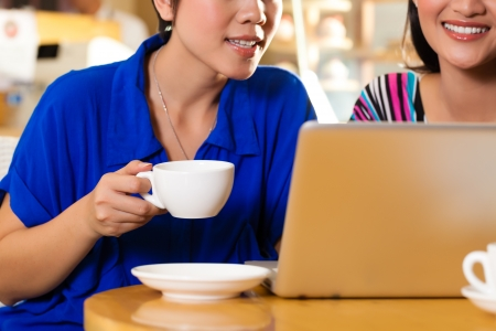 Asian female friends enjoying her leisure time in a cafe, drinking coffee or cappuccino and working on a laptop computer photo