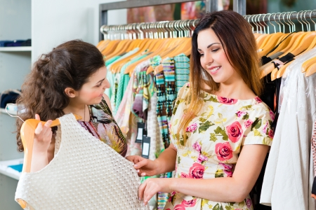 Two female friends having fun while fashion shopping in boutique or store Stock Photo - 21402109