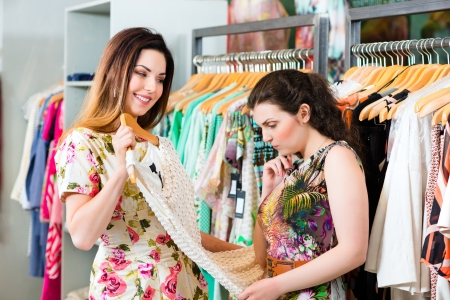 consumerism: Two female friends having fun while fashion shopping in boutique or store